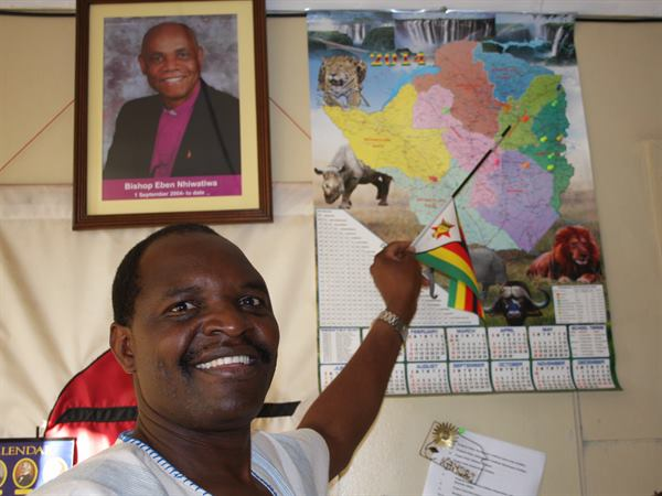 The Rev. Lloyd Nyarota, an Africa University graduate, points to a map of community development projects underway through the Norway-Zimbabwe partnership. Photo by Vicki Brown, UMNS.